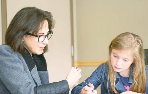 Dr. Deborah Zwick administers a staged psychological test to a school-aged child. Zwick's clients are always kept confidential — that's why the photo is staged and not with a real patient.