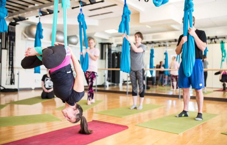 Instructor Tracy Long demonstrates a lotus inversion during a beginner AIReal Yoga class at The Westin in Avon. The lotus inversion, despite appearances, is very safe for beginners to aerial yoga due to the bind that the hammock fabric provides.