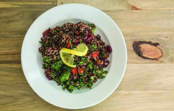 A quinoa bowl with broccoli, kale, beets and tomatoes